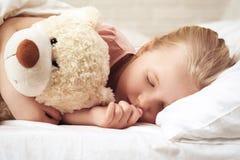 Fille mignonne de petit enfant dormant avec l'ours de nounours photo stock