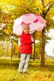 Fille mignonne de sourire tenant le parapluie sous la pluie Photos libres de droits