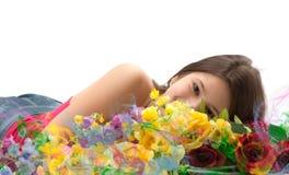 Fille mignonne derrière des fleurs Photos stock