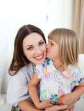 Fille mignonne embrassant sa mère Images libres de droits