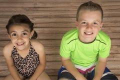 Fille mignonne et garçon s'asseyant sur un sourire du bois de plancher Photo stock