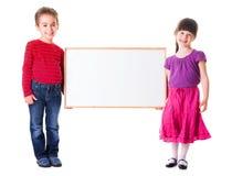 Fille mignonne et garçon tenant l'annonce vide Photo stock