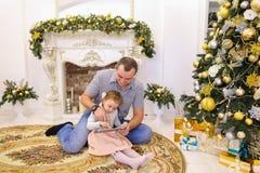 Fille mignonne et papa de papa jouant sur le comprimé se reposant sur le plancher i Image libre de droits