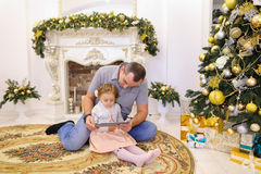Fille mignonne et papa de papa jouant sur le comprimé se reposant sur le plancher i Images libres de droits