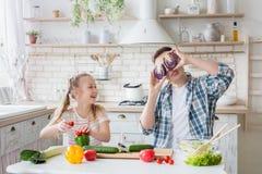 Fille mignonne et son papa ayant l'amusement tout en faisant cuire dans la cuisine photo libre de droits