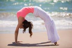 Fille mignonne faisant le yoga à la plage Photographie stock