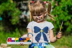 Fille mignonne gaie jouant avec les peintures lumineuses en parc Photographie stock