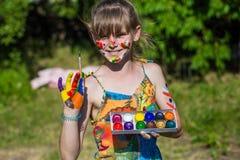 Fille mignonne gaie jouant avec les peintures lumineuses en parc Photo stock