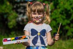 Fille mignonne gaie jouant avec les peintures lumineuses en parc Image stock