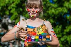 Fille mignonne gaie jouant avec les peintures lumineuses en parc Photos stock