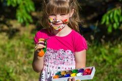 Fille mignonne gaie jouant avec les peintures lumineuses en parc Photos libres de droits