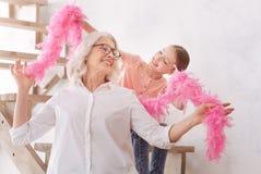 Fille mignonne heureuse aidant sa grand-mère à porter un boa de plume Photos libres de droits