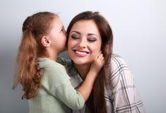 Fille mignonne heureuse d'enfant chuchotant le secret à sa mère riante Photographie stock