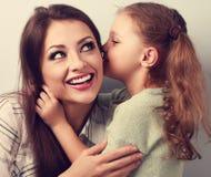 Fille mignonne heureuse d'enfant chuchotant le secret à son rire heureux Photographie stock