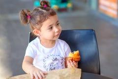 Fille mignonne heureuse sur un caf? mangeant le croissant frais, le jour chaud D?chets z?ro, emballage r?utilisable de papier pou image libre de droits
