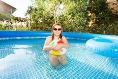Fille mignonne jouant avec du ballon de plage dans la piscine Photographie stock