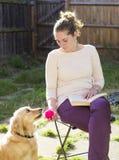 Fille mignonne jouant avec le chien extérieur image libre de droits
