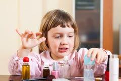 Fille mignonne jouant avec le maquillage photo libre de droits