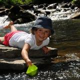 Fille mignonne jouant avec les bateaux de papier Image stock