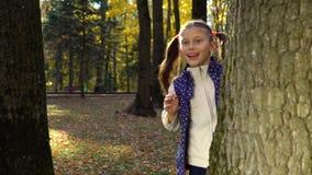 Fille mignonne jouant le cache-cache derrière des arbres en parc d'automne dans le mouvement lent clips vidéos