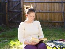 Fille mignonne lisant un livre extérieur photo stock