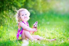 Fille mignonne mangeant la crème glacée dans le jardin Images libres de droits