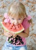 Fille mignonne mangeant la pastèque. Photographie stock libre de droits