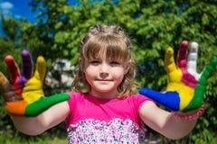 Fille mignonne montrant ses mains peintes dans des couleurs lumineuses Mains peintes blanches de marche Image stock