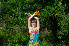 Fille mignonne montrant ses mains peintes dans des couleurs lumineuses Mains peintes blanches de marche Photos stock