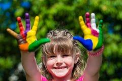 Fille mignonne montrant ses mains peintes dans des couleurs lumineuses Mains peintes blanches de marche Images stock