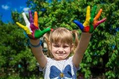 Fille mignonne montrant ses mains peintes dans des couleurs lumineuses Mains peintes blanches de marche Images libres de droits