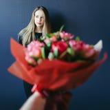 Fille mignonne obtenant le bouquet des tulipes rouges Ami donnant des tulipes Photographie stock