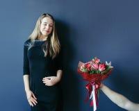 Fille mignonne obtenant le bouquet des tulipes rouges Ami donnant des tulipes Photos stock