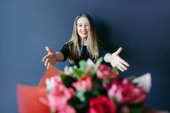Fille mignonne obtenant le bouquet des tulipes rouges Ami donnant des tulipes Photographie stock libre de droits