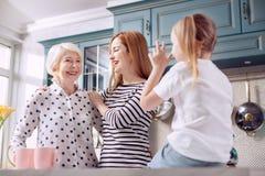 Fille mignonne parlant à sa mère et grand-mère dans la cuisine Image stock
