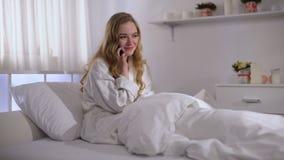 Fille mignonne parlant heureusement au t?l?phone tout en se situant dans le lit, jour de planification avec l'ami clips vidéos