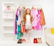 Fille mignonne parmi les robes lumineuses colorées, vêtements Photo stock