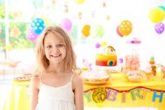Fille mignonne près de table avec des festins à la fête d'anniversaire à l'intérieur image stock