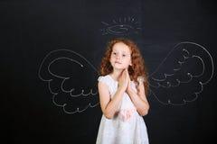 Fille mignonne près des ailes d'ange dessinées sur un tableau noir photographie stock libre de droits