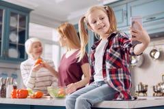 Fille mignonne prenant le selfie dans la cuisine tandis que sa cuisson de parents Photographie stock libre de droits