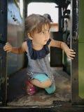 Fille mignonne regardant de vieilles portes de train images stock