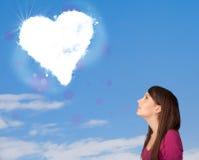 Fille mignonne regardant le nuage blanc de coeur sur le ciel bleu Photos stock