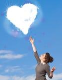Fille mignonne regardant le nuage blanc de coeur sur le ciel bleu Images stock