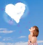 Fille mignonne regardant le nuage blanc de coeur sur le ciel bleu Photo libre de droits
