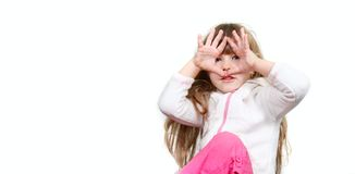 Fille mignonne regardant par ses doigts Image stock