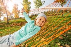 Fille mignonne s'étendant sur le filet de l'hamac en parc Image libre de droits