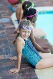 Fille mignonne s'asseyant avec des amis au poolside Photographie stock