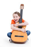 Fille mignonne s'asseyant avec la guitare acoustique. Photographie stock libre de droits