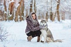 Fille mignonne s'asseyant avec le chien de traîneau de chien sur le fond de la forêt Photographie stock libre de droits