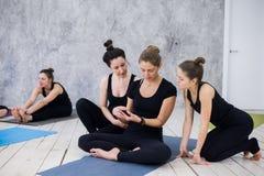Fille mignonne s'asseyant et ayant une vie sociale avec le groupe après leur classe de yoga photo libre de droits